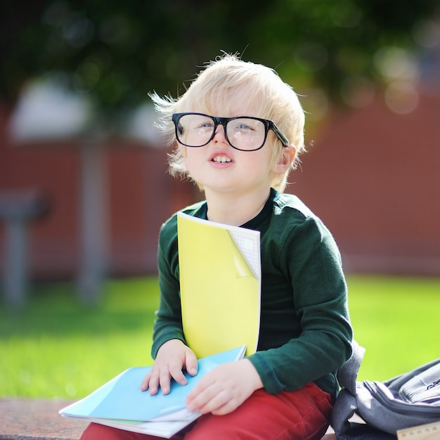 Cute little schoolboy studying outdoors on sunny day. back to school concept. Premium Photo