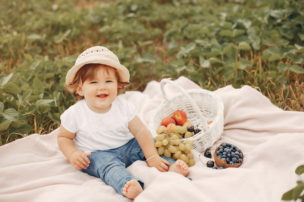 Cute little sitting on a blanket in a park Free Photo