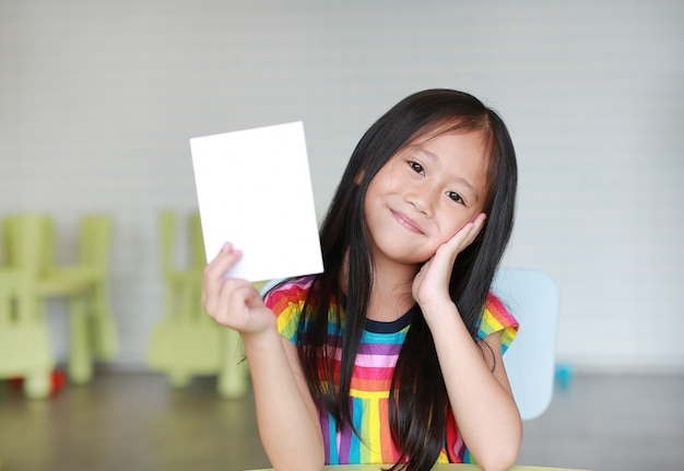 Cute little smiling asian child girl holding blank white paper card in her hand Premium Photo