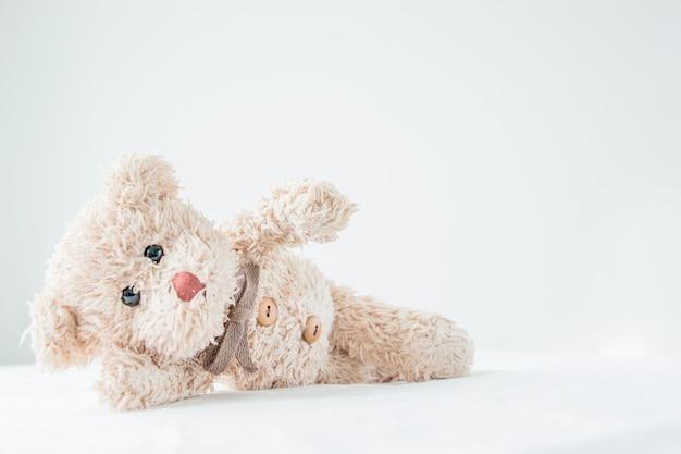 Cute little teddy bear lay down on the bed. Premium Photo