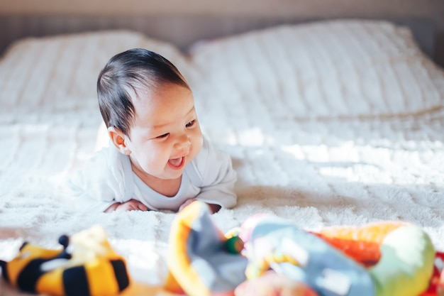 Cute little three month old baby girl, playing at home in bed in bedroom Premium Photo