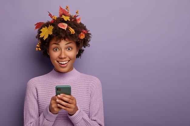 Carina e adorabile ragazza dalla pelle scura tiene il cellulare moderno, guarda direttamente la telecamera, sta per fare una telefonata, sorride felice, vestita con un vestito casual, posa durante il periodo autunnale, isolato sul muro viola Foto Gratuite