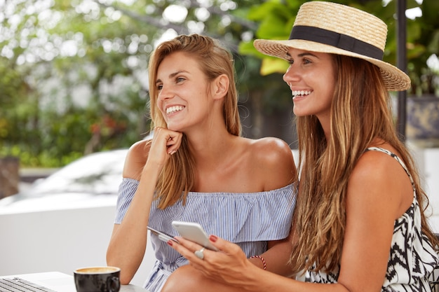 陽気な笑顔のかわいい素敵な若い女性は自由にカフェテリアで過ごし、オンラインコミュニケーションと娯楽のために近代的なテクノロジーと高速インターネットを使用しています。ライフスタイルとレジャーのコンセプト 無料写真