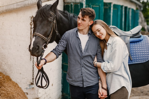 Cute loving couple with horse on ranch Free Photo