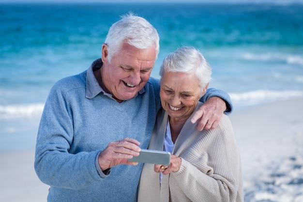 Cute mature couple looking at smartphone Premium Photo