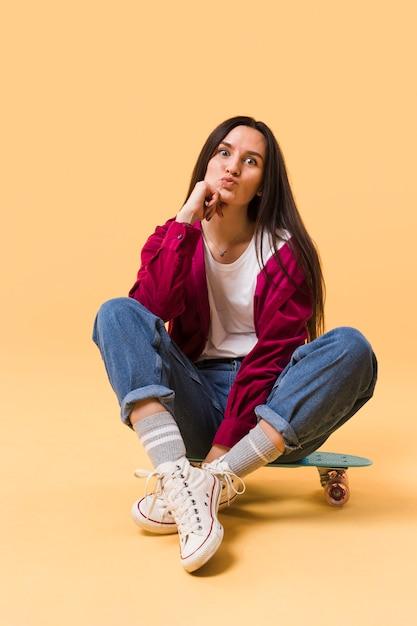Cute model sitting on skateboard Free Photo