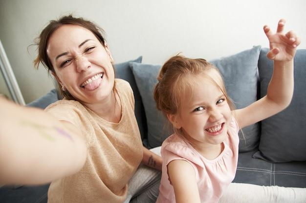 Симпатичные мама и дочь делают селфи и дурачатся в камере телефона. Premium Фотографии