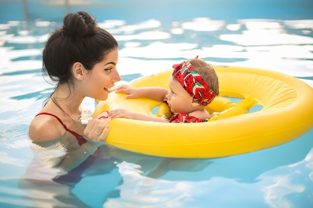 Cute mother swimming in the swimming pool with her baby Premium Photo