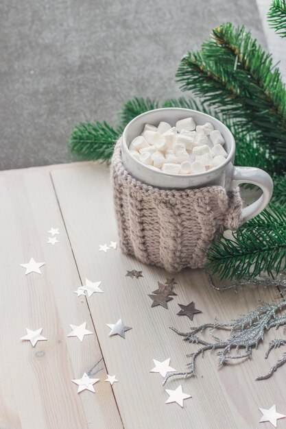 Tazza carina piena di marshmallow circondato da decorazioni natalizie sul tavolo Foto Gratuite