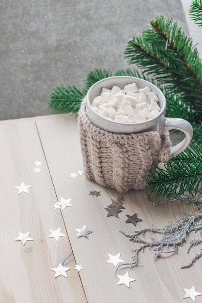 テーブルの上のクリスマスの装飾に囲まれたマシュマロがいっぱいのかわいいマグカップ 無料写真