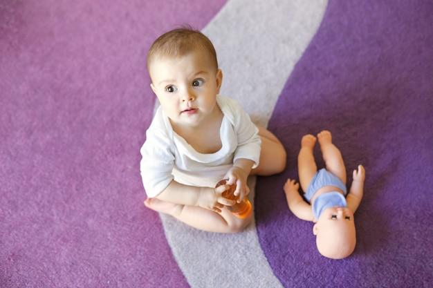 人形と紫のカーペットの上に座ってかわいい素敵な赤ちゃん女性。 無料写真