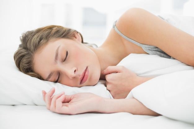 Симпатичная мирная женщина, дремлет, лежащая под покровом на кровати Premium Фотографии
