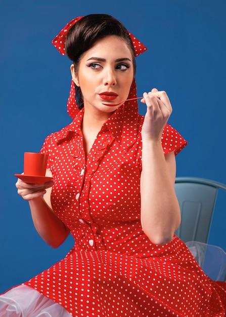 青いスタジオでポーズをとるかわいいピンナップガール 無料写真