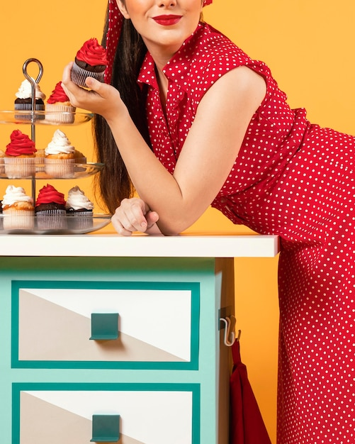 いくつかのカップケーキの隣に立っているかわいいピンナップガール 無料写真