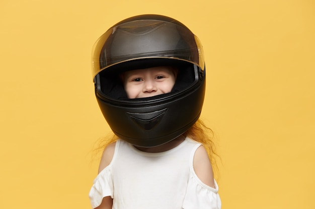 Cute playful little girl wearing black motorcycle helmet taken from her father. funny female child posing isolated in protective motor equipment,  with smile Free Photo
