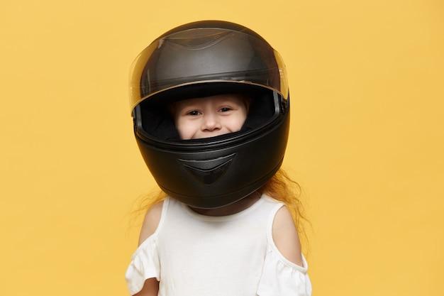 Cute playful little girl wearing black motorcycle helmet Free Photo