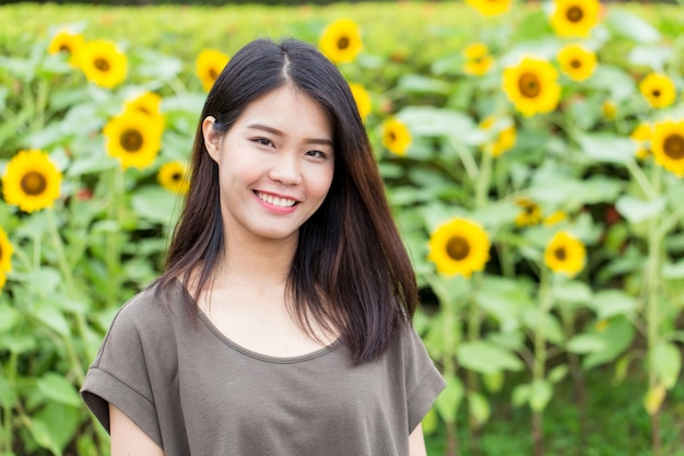 Cute portrait asian thai teen smile with sunflower with copy space. Premium Photo