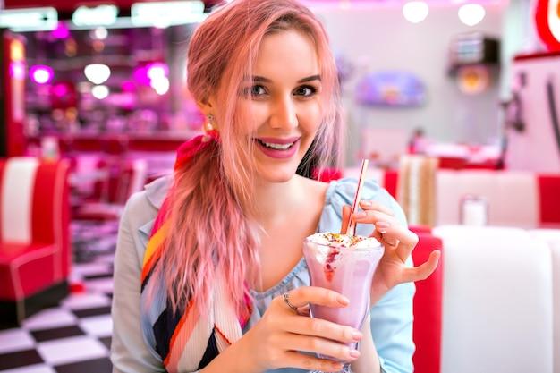 トレンディなピンクの髪のかわいいかなり官能的な女性は、彼女の甘いイチゴのミルクシェイク、笑顔、ファッショナブルなヴィンテージパステル衣装をお楽しみください 無料写真
