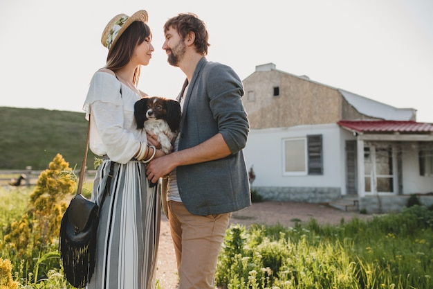 Cute pretty stylish hipster couple in love walking with dog in countryside, summer style boho fashion, romantic Free Photo
