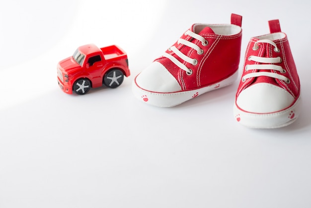 Cute red small sized canvas shoes with toy car top view on white with copyspace Premium Photo