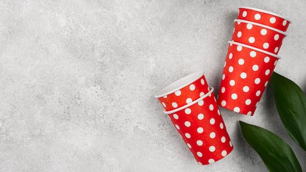 Симпатичные красные с белыми точками чашки и растения Бесплатные Фотографии