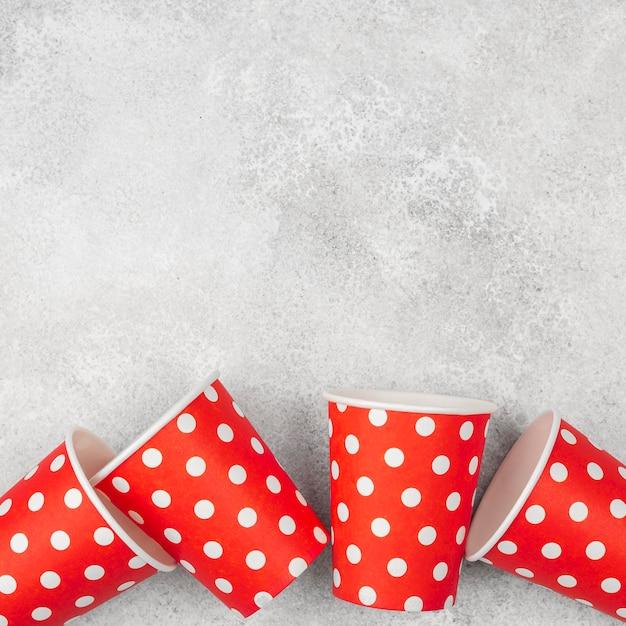 Симпатичные красные с белыми точками чашки копируют пространство Бесплатные Фотографии