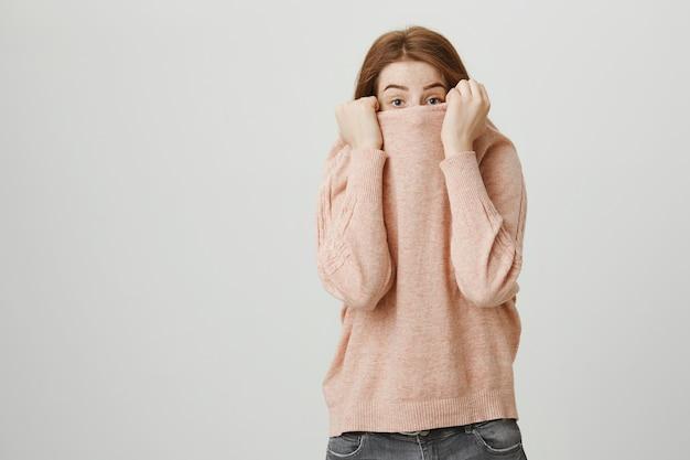 Cute redhead teenage girl hide face over sweater, peeking Free Photo