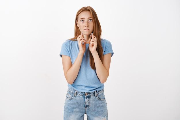 La donna dai capelli rossi carina spera che dio ascolti le preghiere che si morde il labbro inferiore mentre si trova intensamente sul muro grigio, incrociando le dita per buona fortuna mentre desidera passare gli esami ed entrare nella famosa università Foto Gratuite