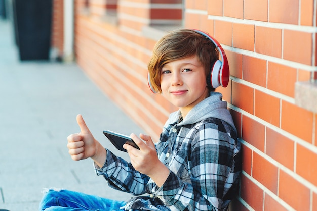 Cute schoolboy with wireless headphones listens to the music at break time in school Premium Photo