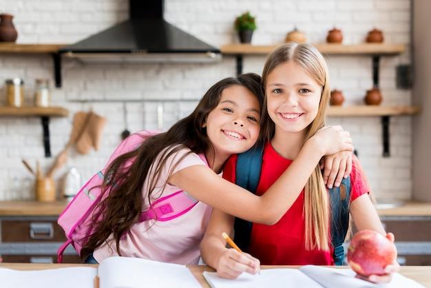 Симпатичные школьники с рюкзаками, сидя за столом и делать домашние задания дома Бесплатные Фотографии