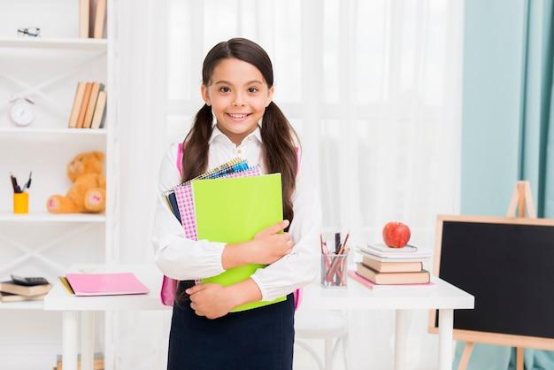 教室でメモ帳を保持している制服を着たかわいい女子高生 無料写真