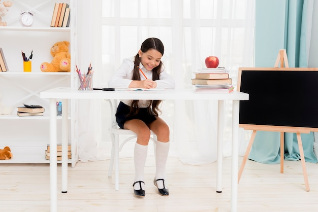 Cute schoolgirl sitting at desk and exercising in classroom Free Photo