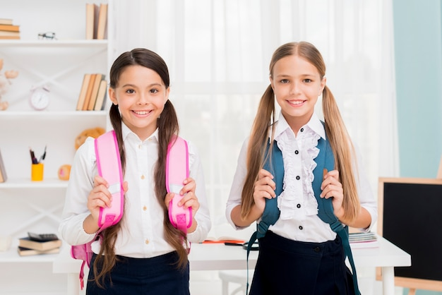 Cute schoolgirls with backpacks standing in classroom Free Photo