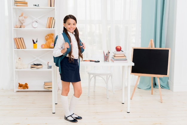 Cute schoolkid with backpack standing in front of desk at classroom Free Photo