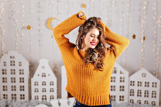 Милая, застенчивая девушка скромно улыбается и позирует с поднятыми руками в уютном интерьере, оформленном на новый год. Бесплатные Фотографии