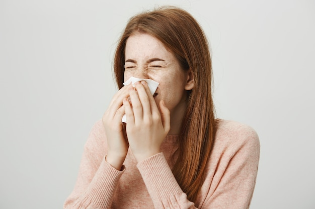Cute sick redhead girl with allergy sneezing in napkin Free Photo