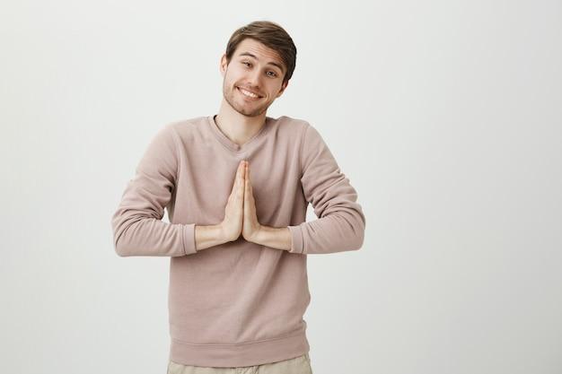 Simpatico uomo sciocco sorridente che implora, tieni le mani in preghiera, supplica o dì per favore Foto Gratuite
