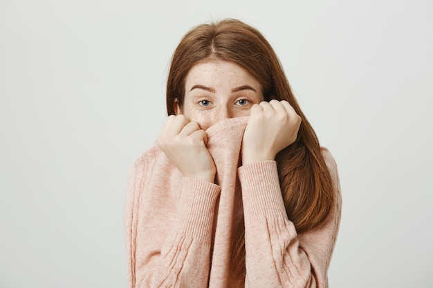 Cute silly redhead woman hiding face behind sweater collar and look shy Free Photo