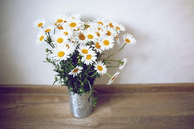 明るい部屋とフローリングの床に白い鎮静を施したかわいい銀製の花瓶。ぼろぼろのシックなスタイル。 無料写真