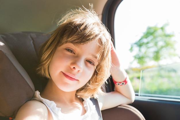 Милый маленький ребенок, белокурая девочка, в автокресле надевает ремни безопасности, собирается идти по дорожке дороги, отражая солнечный свет Premium Фотографии