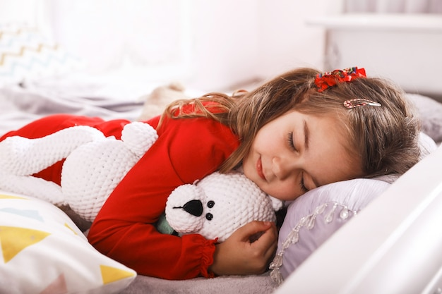 Cute small girl is sleeping with a white bear toy dressed in the red pajamas Free Photo