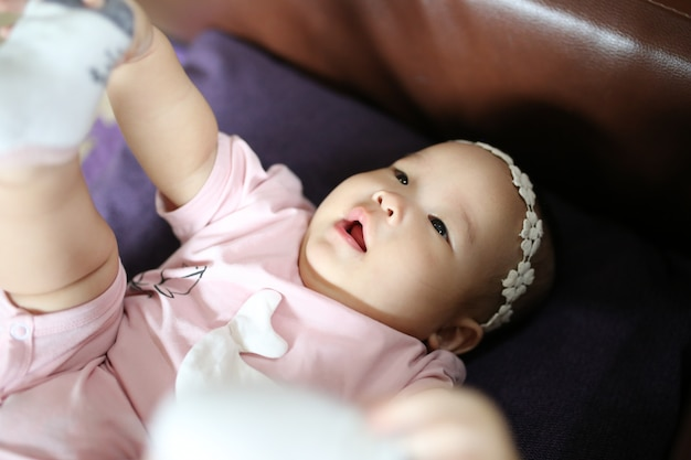 Cute smart asian newborn baby sleeping with teddy rabbit toy on pink soft bed at home. Premium Photo
