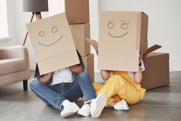 Sorrisi carini sulle scatole che è sulle teste. coppia felice insieme nella loro nuova casa. concezione del movimento Foto Gratuite