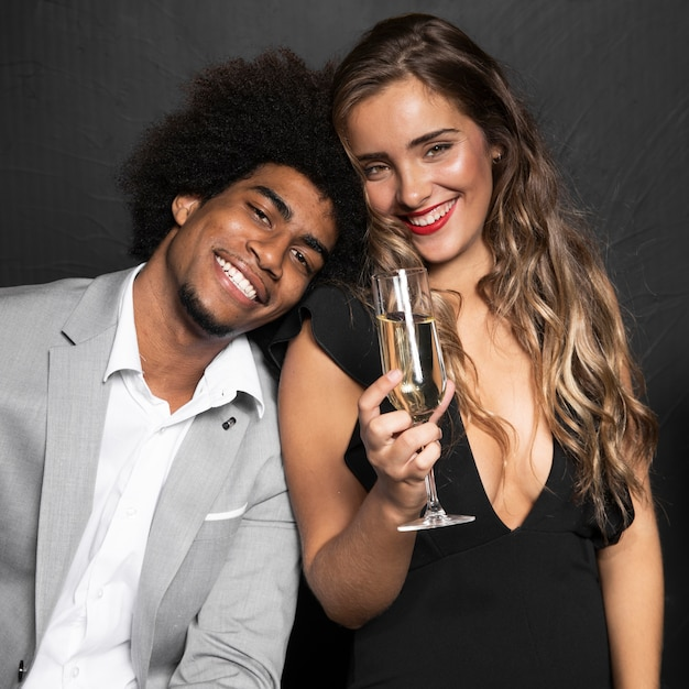 Cute smiley couple holding a glass of champagne Free Photo