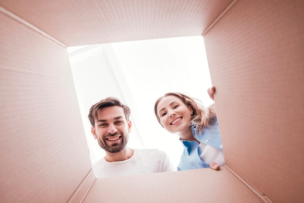 Cute smiley couple inside bottom of the box view Free Photo