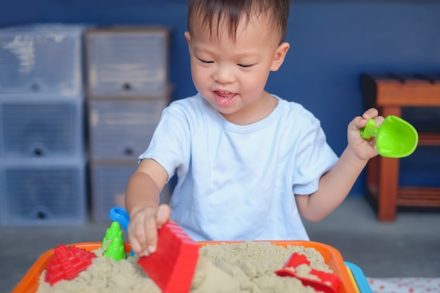 Cute smiling asian 2 years old toddler boy playing with kinetic sand in sandbox at home / nursery / day care Premium Photo