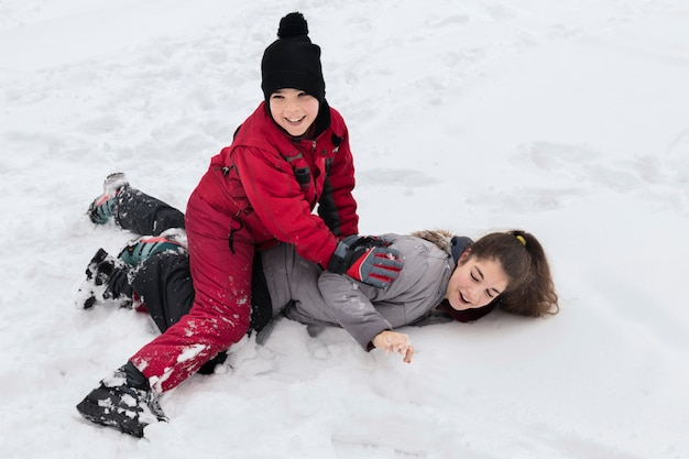 Cute smiling boy playing with her sister on snowy land at winter day Free Photo