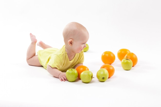 Cute smiling healthy child lies among frui Premium Photo