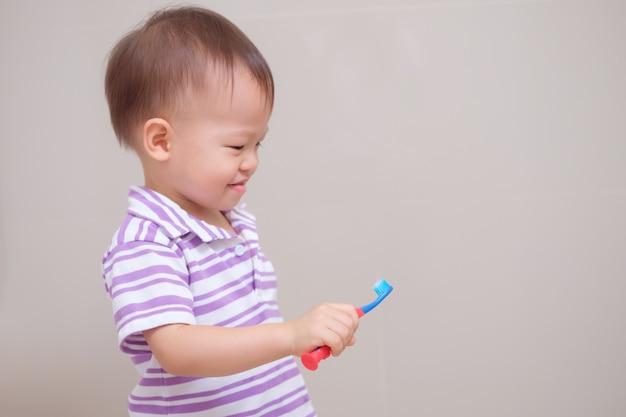 Симпатичный улыбающийся маленький азиатский мальчик-малыш в фиолетовой рубашке, держащий зубную щетку, и учится чистить зубы в ванной дома Premium Фотографии