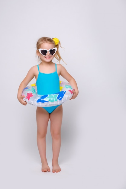 Cute smiling little girl in swimsuit with rubber ring isolated on white Premium Photo